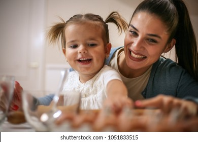 Mother and daughter in kitchen. Mother and daughter baking cookies together.