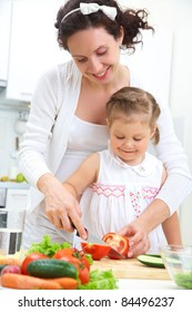 Mother and daughter in kitchen making a salad