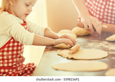 Mother and daughter in the kitchen preparing croissants to bake.