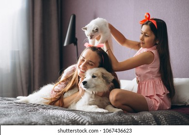 Mother and daughter with kitten and dog