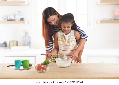 Mother and daughter kneading dough together in kitchen