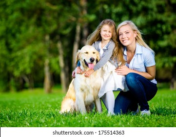 Mother and daughter with labrador retriever sitting on the grass at the summer park