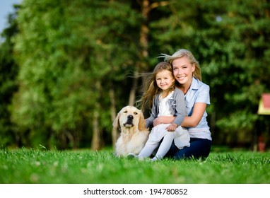 Mother with daughter and labrador sitting on the green grass at the summer park