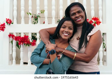 Mother and daughter laughing in an outdoor embrace