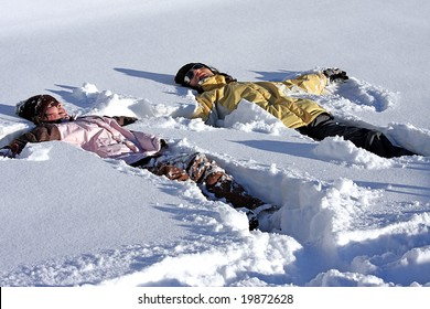 Mother and daughter laying together in the powder snow