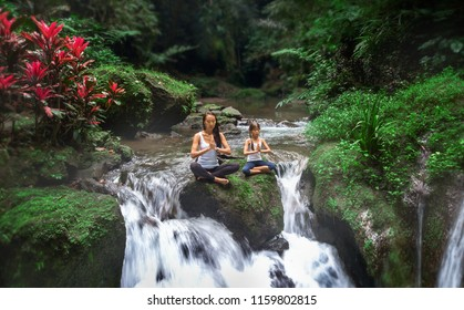 Mother with daughter learn the practice of meditation, thoughts and concentration, waterfall and jungle around,nature of Bali island