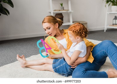 mother and daughter learning alphabet on floor at home