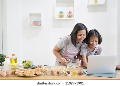 Mother and daughter learning online cooking using laptop computer in the kitchen at home, happy family asian concept