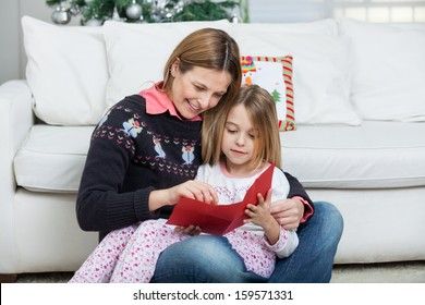 Mother and daughter with letter sitting at home during Christmas