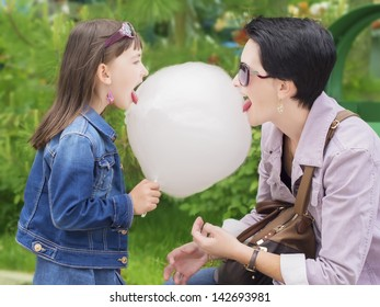Mother and daughter lick cotton candy