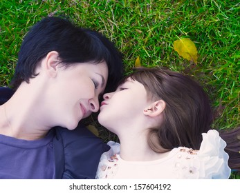 Mother and daughter lie on the grass