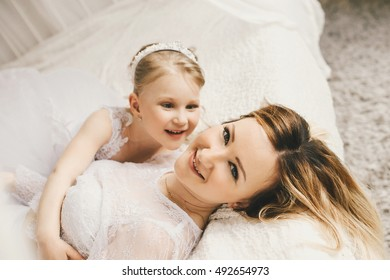 Mother and daughter like brides in white dress on the bed.