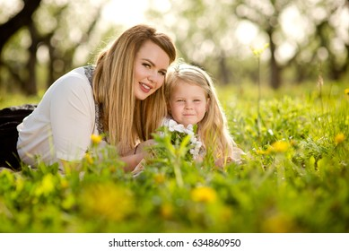 Mother with daughter a little blond girl, lying in the garden or park on the grass with flowers, love, family, communication