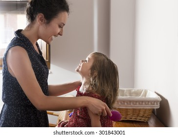 Mother and daughter look at each other smiling and happy. Woman combing the hair of little girl in the morning. Concept of family and happiness
