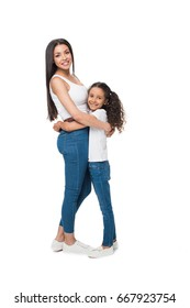 mother and daughter looking at camera while hugging each other isolated on white