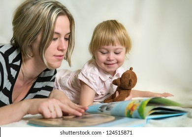 Mother and daughter looking at children's book