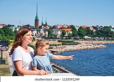 Mother and daughter looking at sea from restaurant terrace, Helsinki on background.