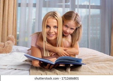Mother and daughter lying in bed and read book