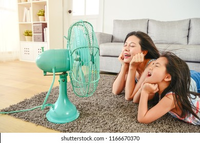 mother and daughter lying in front of fan. refreshing their faces from hot weather. half-body view from side.