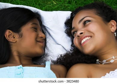 Mother and daughter lying in the grass having fun