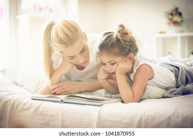Mother and daughter lying on bed and reading book.
