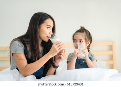 Mother and daughter are lying on bed and drinking milk.Glass of milk for mother and daughter at home