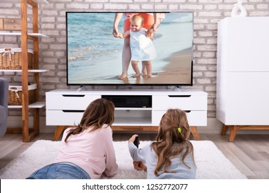 Mother And Daughter Lying On Carpet Watching Television At Home
