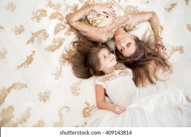 Mother and daughter lying on the floor in a beautiful white dress.