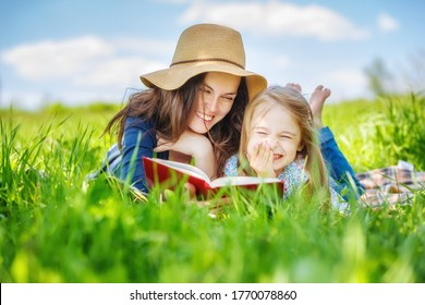 Mother and daughter lying on green grass enjoy reading book