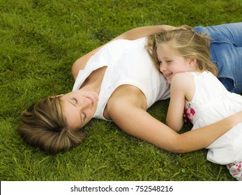 A mother and daughter lying on a lawn