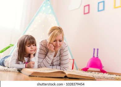 Mother and daughter lying on a playroom floor, reading a fairy tale. Focus on the mother