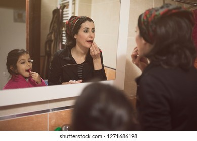 Mother and daughter make up their lips