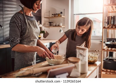 Mother and daughter making apple pie dough in the kitchen while daughter pouring water into flour