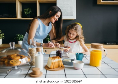 Mother and daughter making breakfast together at home