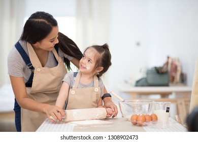 Mother and daughter making cookies together. Girl is to challenge the cookie making with mother