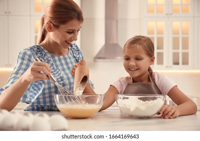 Mother and daughter making dough together in kitchen