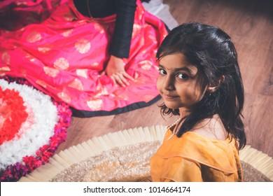 Mother and daughter making flower rangoli and girl lighting diya or samai