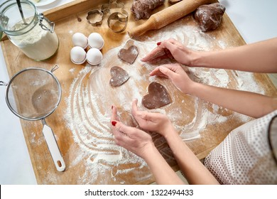 Mother and daughter making heart shape with hands. Heart shaped cookies of chokolate dough on pastry board. Sifted flour and eggs and kitchen tools for homemade pastry.