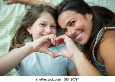 Mother and daughter making heart shape from hand while lying on bed at home