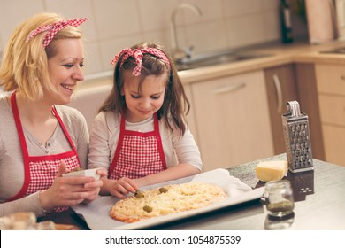 Mother and daughter making pizza in the kitchen; little girl putting olives on top of a pizza ready for baking. Focus on the daughter