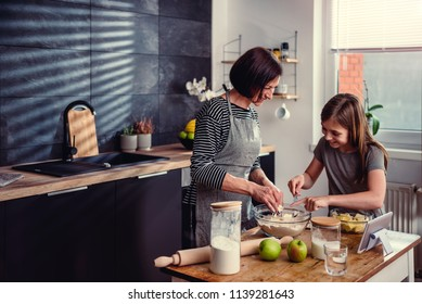 Mother and daughter making together dough for apple pie at kitchen