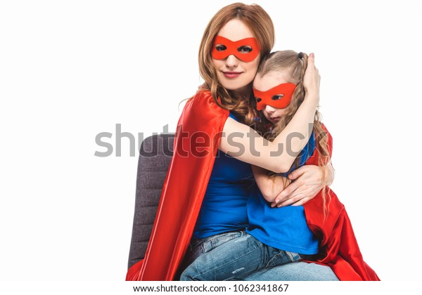 mother and daughter in masks and cloaks hugging isolated on white