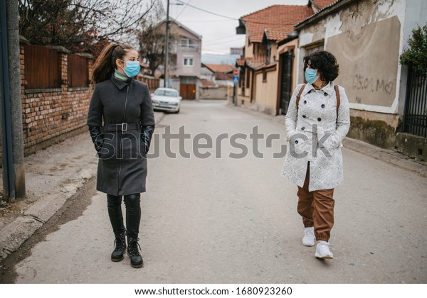 Mother and daughter with masks walking and talking on the street