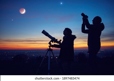 Mother and daughter observing stars, planets, Moon and night sky with astronomical telescope.