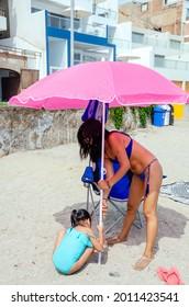 Mutter und Tochter am Strand, die einen Regenschirm in den Sand legen
