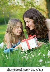 Mother and daughter on green grass with a gift box