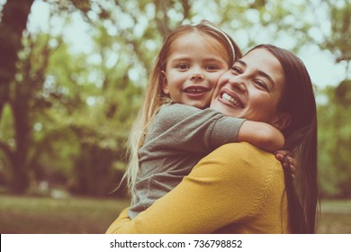 Mother and daughter on meadow. Mother and daughter hugging. Head shoot.