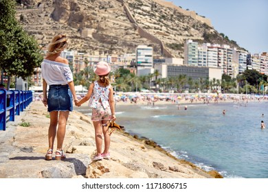 Mother and daughter on the Postiguet beach at summer, rear view. Mother showing to the Santa Barbara castle, fortification in Alicante city. Swimming and sunbathing tourists. Costa Blanca. Spain