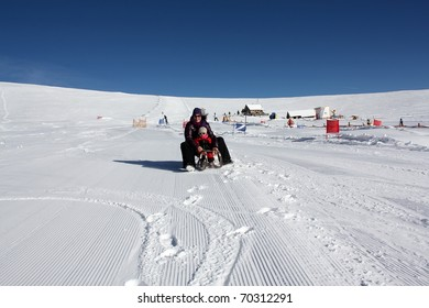 mother and daughter on the sled