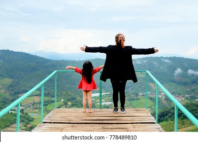 mother and daughter open arms with freedom feelling in the mountain peak